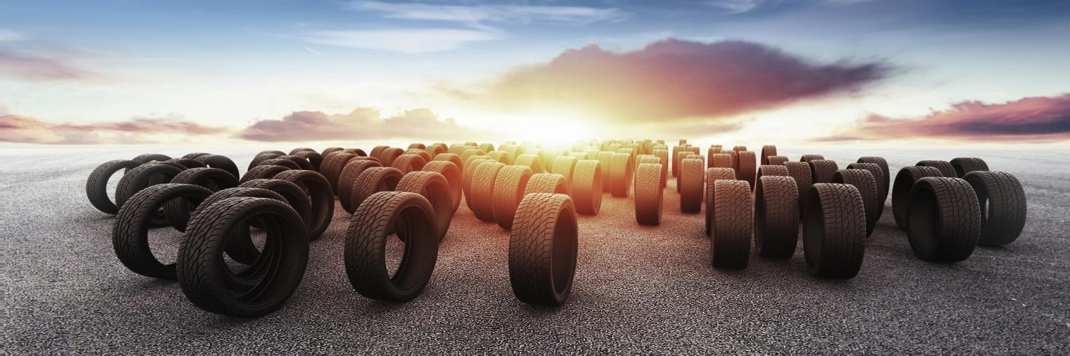 a lot of tires on pavement with a sunset in the background